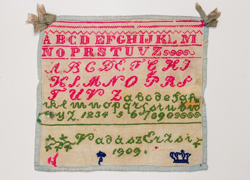 Keresztszemes öltésekkel hímzett mintakendő. Készítette Vadász Erzsi 1909-ben