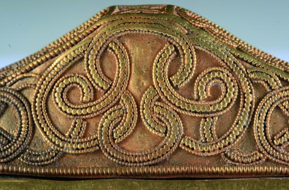 Aranyból készült, szalagornamentikával díszített, hármas tagozódású kardmarkolat. Kalapált aranylemez. Méretei: h.: 87 mm, sz.: 25 mm, m.: 25 mm. (Leltári szám: 66.37.1.1.)
