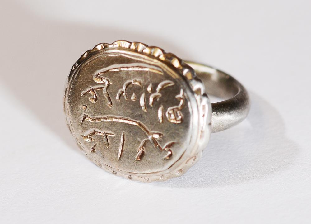 Öntött ezüst gyűrű, palástjának szélén körben hullámvonalas díszítés található, ovális alakú pecsétlő részén vésett felirattal